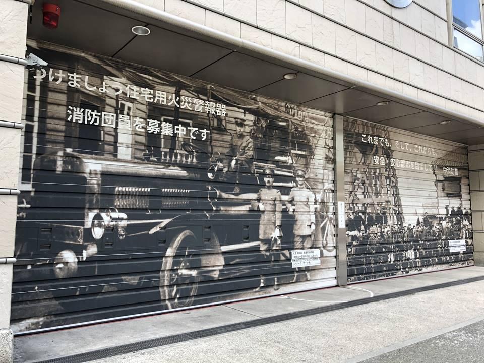 山下消防出張所のシャッターに描かれている日本初のポンプ車を備えた消防隊写真