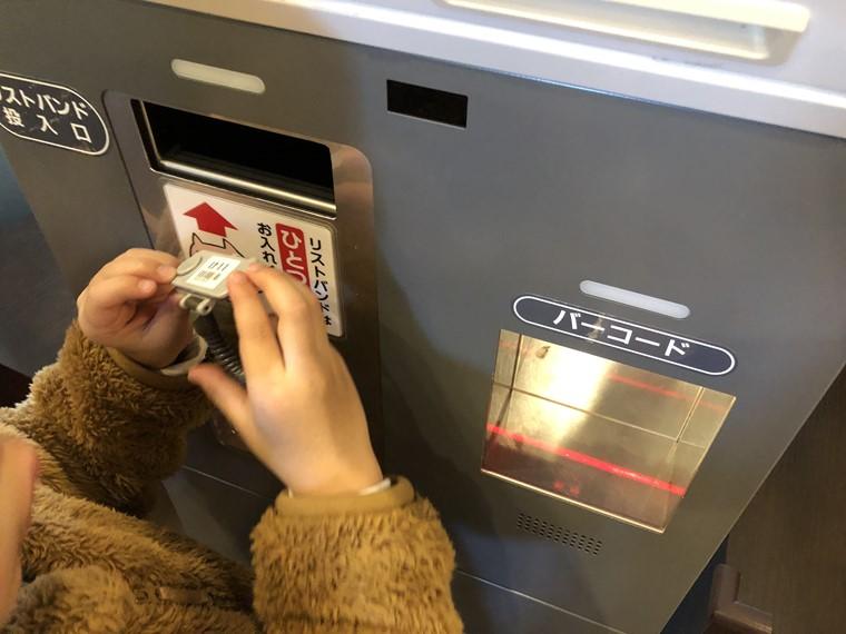 万葉の湯町田館の自動精算機にリストバンドを返却する様子